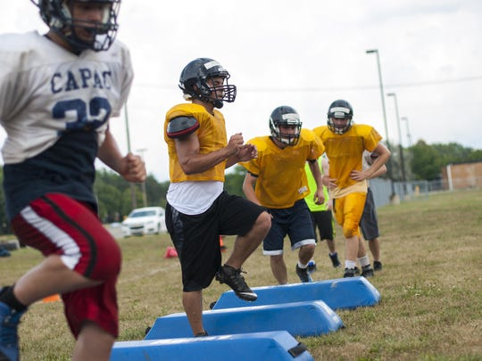 Members of the Capac varsity football team run through a drill Thursday, Aug 11, during football practice at Capac High School.