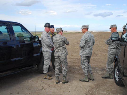 Montana National Guard officials discuss the progress on the dirt landing strip at the Great Falls airport that will be used for C-130 training.