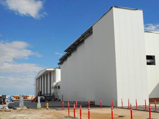 Construction on the new hangar, foreground, and the existing hangar is nearing completion.