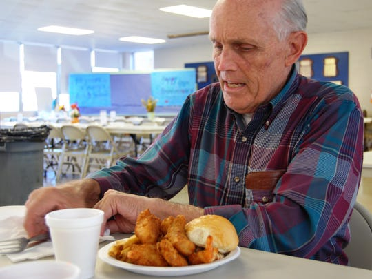 Dick Serreyn, of St. Clair, prepares to dig into his fish dinner Friday at the St. Mary's Fall Festival in St. Clair.