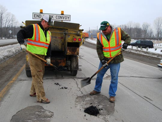 Greg Gooch, left, and Bill Muggelberg of the St. Clair County Road Commission patch potholes on Dove Road in Port Huron Township.