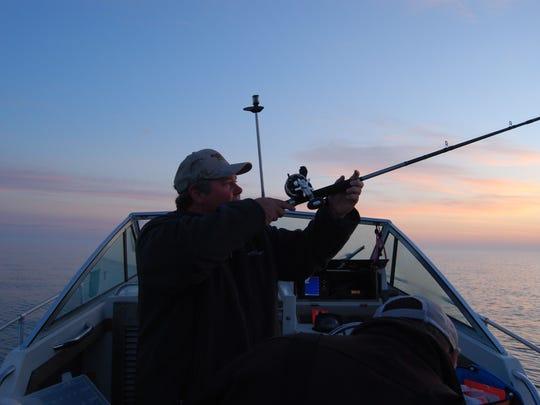 Jim Frazer, captain of the Double Down, checks a rod before rigging it up during a salmon and trout fishing trip on Lake Huron.