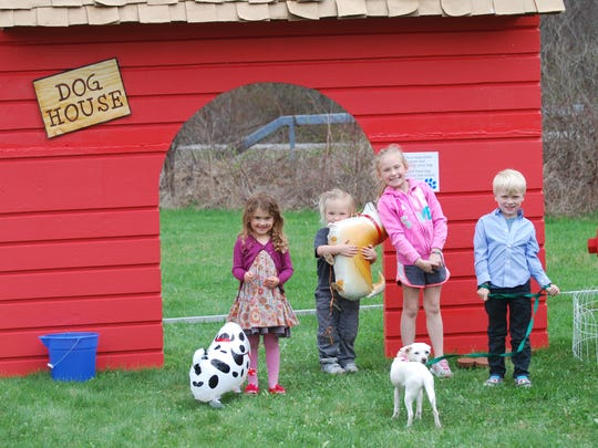 """Young Dutchess Day School students and siblings – and their dogs – await the dog walk next to the giant """"dog house."""""""