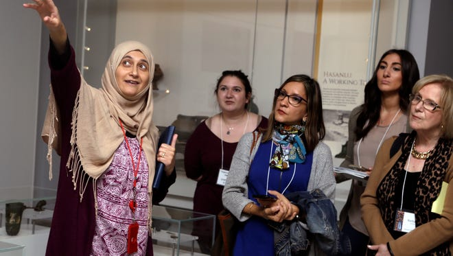 In this April 26, 2018 photo, Moumena Saradar, left, originally from Syria, guides visitors through the Middle East gallery at Penn Museum, in Philadelphia. The University of Pennsylvania Museum of Archaeology and Anthropology is in the midst of dramatic renovations, opening new galleries to showcase previously undisplayed items, telling the stories of those artifacts in more relatable ways and adding guides native to the parts of the world being showcased.