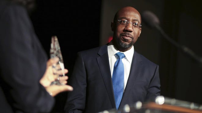 """FILE - In this Jan. 13, 2017, file photo, Pastor Raphael Gamaliel Warnock, of Ebenezer Baptist Church, receives a """"President's Fulfilling the Dream Award"""" during during a Martin Luther King Celebration at the Tate Student Center at the University of Georgia in Athens, Ga. In response to Martin Luther King's teachings about love and hate, Warnock says that now """"is a time of moral reckoning in our nation. We must choose to stand on the side of light and love."""""""