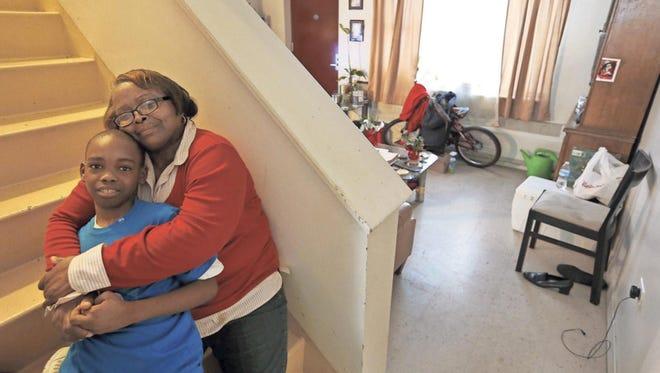 Debra Aldridge and her grandson, Mario Hendricks, share a hug at their home on Chicago's South Side.