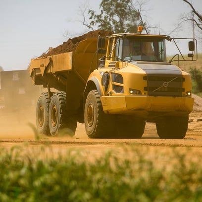 Dirt flies through the air as a construction truck