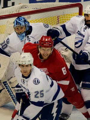 Red Wings forward Justin Abdelkader battles with Tampa Bay's Matthew Carle and Jason Garrison during the first period of the Wings' 3-2 overtime loss Thursday at Joe Louis Arena.