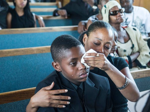 Sharon Lamb comforts her son Kasai Hayden, 10, extended family of the deceased Michelle Cusseaux, as they mourn their during the funeral services at Emmanuel Church Of God In Christ in Phoenix on August 23, 2014. Cusseaux, was mentally ill Phoenix woman was slain by Phoenix police.