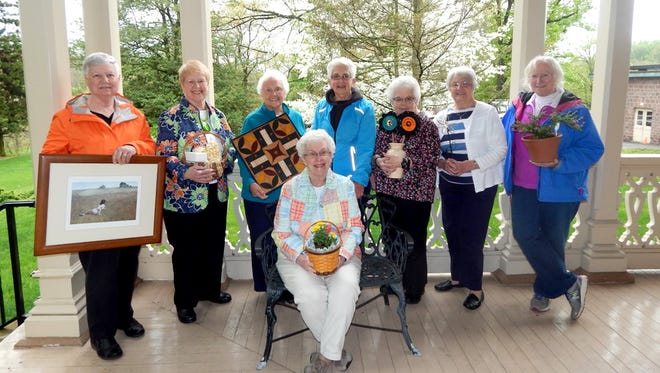 Cornwall Manor residents showcase silent auction, food, craft and plant items that will be available for sale at the May 7 Cornwall Manor Society Blooms & More Festival. Pictured are, from left, Judy Borger, Pauline Charles, Patricia O'Neill, Ellen Arnold (seated), Joan Hanna, Sally Renda, Patricia Walter, and Cecilia Haberzettl. The community is invited to attend the festival from 9 a.m. to 2 p.m. on the Buckingham Campus at Cornwall Manor Retirement Community. The event is held rain or shine because a majority of the festival is held indoors. There is no admission fee. Attendees should park at Sacred Heart Catholic Church in Cornwall for bus transportation to the festival.