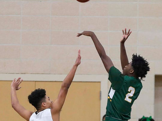 Dominican's Abe Scruggs (left) tries to block a shot by  Martin Luther's  Ace Evans (2) during the boys basketball game between Dominican and Martin Luther at Dominican in Whitefish Bay, Friday, Jan. 19, 2018.