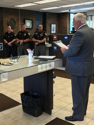 Martin Sutter, GenoaBank president, recognizes local law enforcement officers with a proclamation of appreciation.