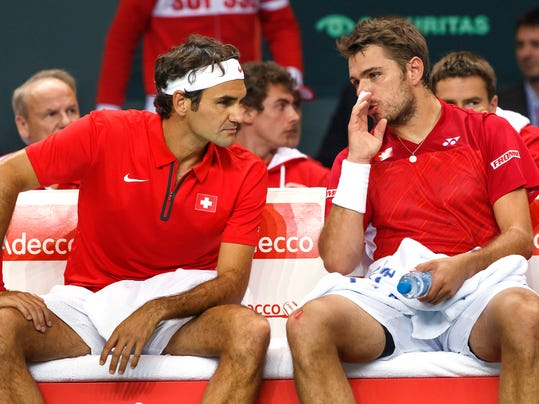 Switzerland's Stanislas Wawrinka, right, speaks with his doubles partner Roger Federer, left, during their doubles match of the Davis Cup World Group Quarterfinal match between Switzerland and Kazakhstan  in Geneva, Switzerland, Saturday, April 5, 2014.  Roger Federer and Stanislas Wawrinka lost the doubles match to Andrey Golubev and Aleksandr Nedovyesov on Saturday, giving Kazakhstan a 2-1 lead over Switzerland in the Davis Cup quarterfinals. (AP Photo/Keystone,Salvatore Di Nolfi)