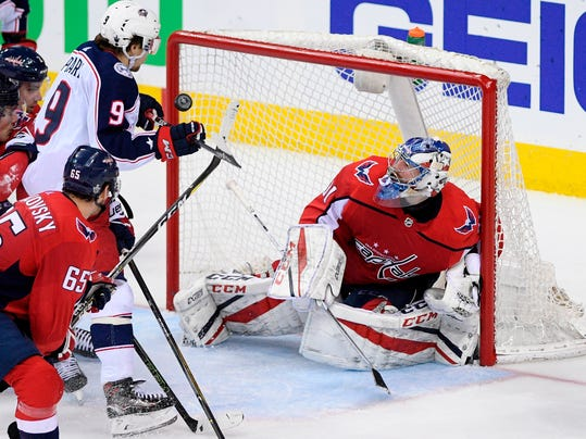 Columbus Blue Jackets left wing Artemi Panarin (9), of Russia, vies for the puck against Washington Capitals goaltender Philipp Grubauer (31), of Germany, during the third period in Game 1 of an NHL first-round hockey playoff series, Thursday, April 12, 2018, in Washington. Also seen is Capitals left wing Andre Burakovsky (65). The Blue Jackets won 4-3 in overtime. (AP Photo/Nick Wass)