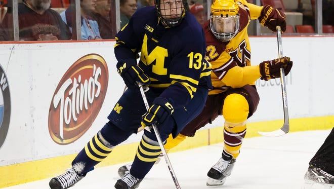 Michigan's Zach Werenski (13) skates with the puck near Minnesota's Travis Boyd in the first period during an NCAA college hockey game in the Big Ten Conference tournament Saturday, March 21, 2015, in Detroit.