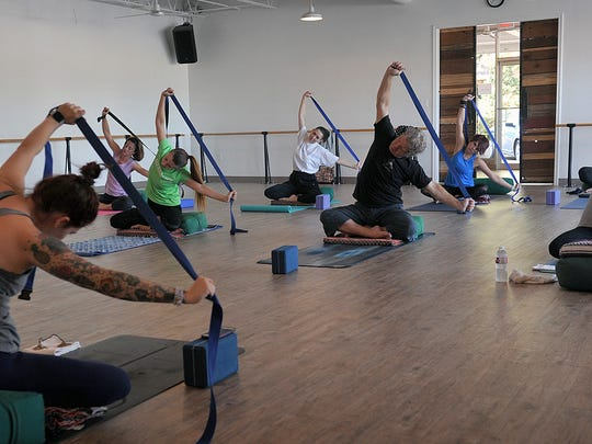 A yoga class, lead by new studio owner Carson Ford, uses elastic bands during a series of movements in this Times Record News file photo from 2017.