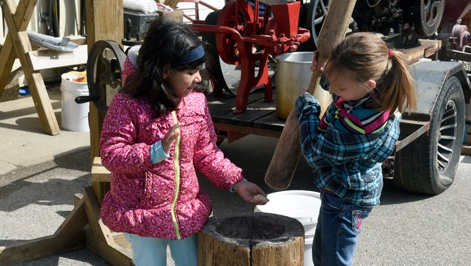 India Vannatter, 6, left and Myranda Smith 8, work together to create corn meal while attending the annual Spring Farm Fest at Angel Mounds State Historic Site in Evansville Saturday.
