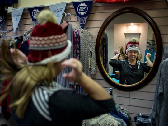 Maggie MacKenzie, of Lexington, tries out a hat at Suzanne's during Small Business Saturday Nov. 26 in downtown Port Huron.