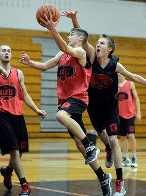 North Buncombe's Andrew Garrett goes in for the block as his teammate Brent Sherwood drives to the basket during Monday's practice.