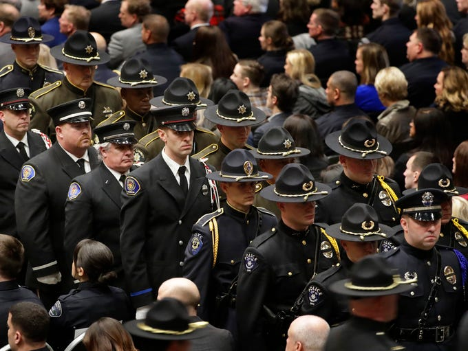 Members of a law enforcement honor guard stand at attention
