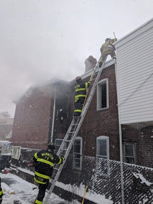 Wilmington firefighters try to put out the Maryland Avenue fire Wednesday afternoon amidst heavy snowfall.