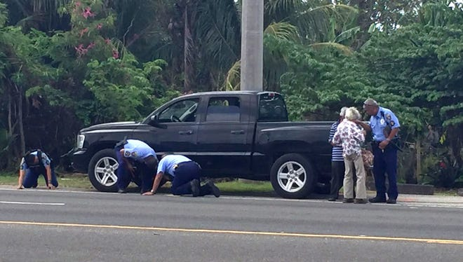 Guam Police Department officers examine the underside of a Dodge Dakota.