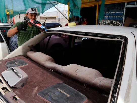 A worker prepares to replace a car's broken window.
