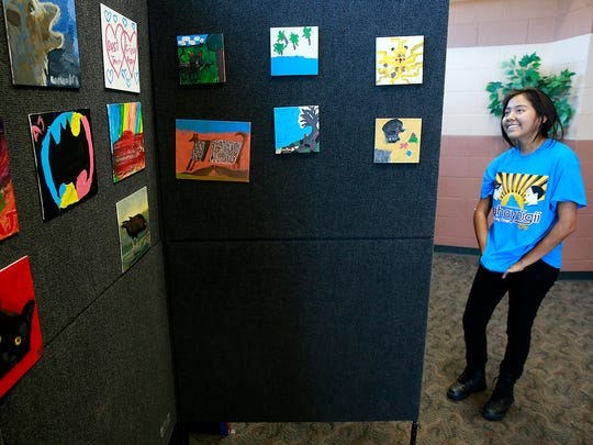 """Amari Jones, 14, who lives near Teec Nos Pos, Ariz., talks about her paintings during the """"Dahayóígíí"""" art event on Friday at the Phil L. Thomas Performing Arts Center in Shiprock."""