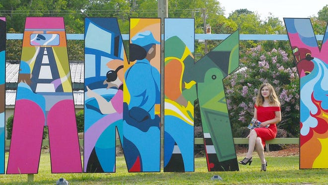 Artist Sophie Docalavich with the Allendale Hometown Heroes tribute she created.