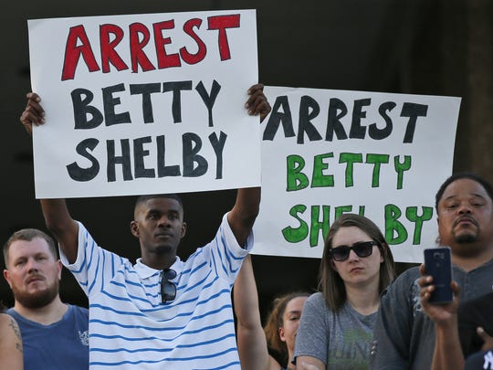 """People hold signs at a """"protest for justice"""" over Friday's shooting death of Terence Crutcher, sponsored by We the People Oklahoma, in Tulsa, Okla., Tuesday, Sept. 20, 2016. (AP Photo/Sue Ogrocki)"""