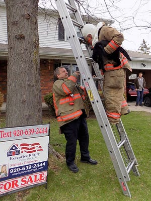 De Pere Fire Capt. Ed Balcer holds the ladder as firefighter Tom Nelson climbs down after rescuing Sidney the cat from a tree on the city's southeast side on Tuesday.