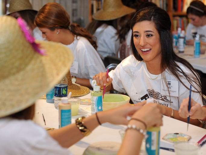 Miss Petal, Nicolet Hopper, 21, right, smiles as she talks with other Miss Hospitality contestants as they paint ceramic bowls for the Empty Bowls fundraiser at Main Street Books in Hattiesburg.