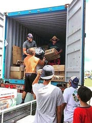 Mixed martial arts star Frank Camacho helps unload a container of donated supplies to  provide aid to Saipan following Super Typhoon Soudelor.
