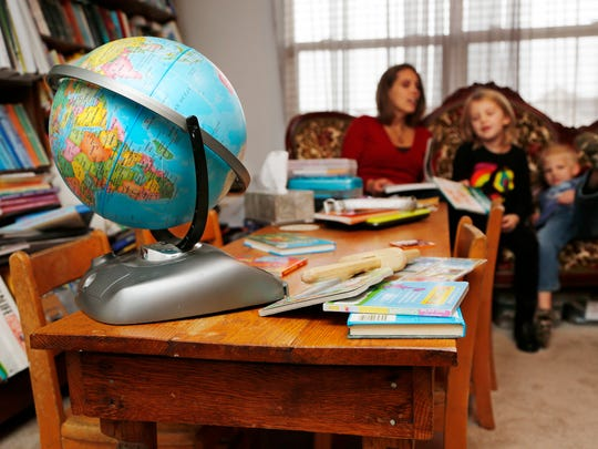 Cara Putman reads with her daughter Rebecca, 6, and son Daniel, 4, Monday, November 24, 2014, in their Lafayette home. An upstairs room in the serves as the homeschooling classroom for all four Putman children. Cara Putman was homeschooled as a child growing up in Nebraska.