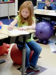 Alexis Davidson rest comfortably on her red ball seat while filling out her assignment paper at Clyde Elementary School.