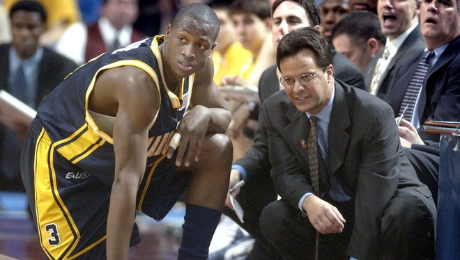 Tom Crean and Dwyane Wade talk during a Marquette NCAA Tournament game in 2003.