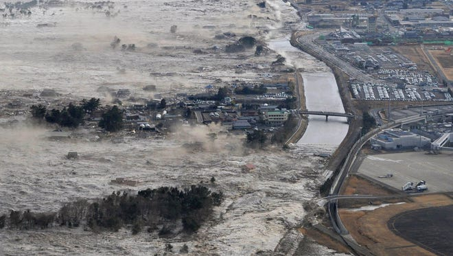 An earthquake-triggered tsunami sweeps the shores along Iwanuma in northern Japan on March 11, 2011.