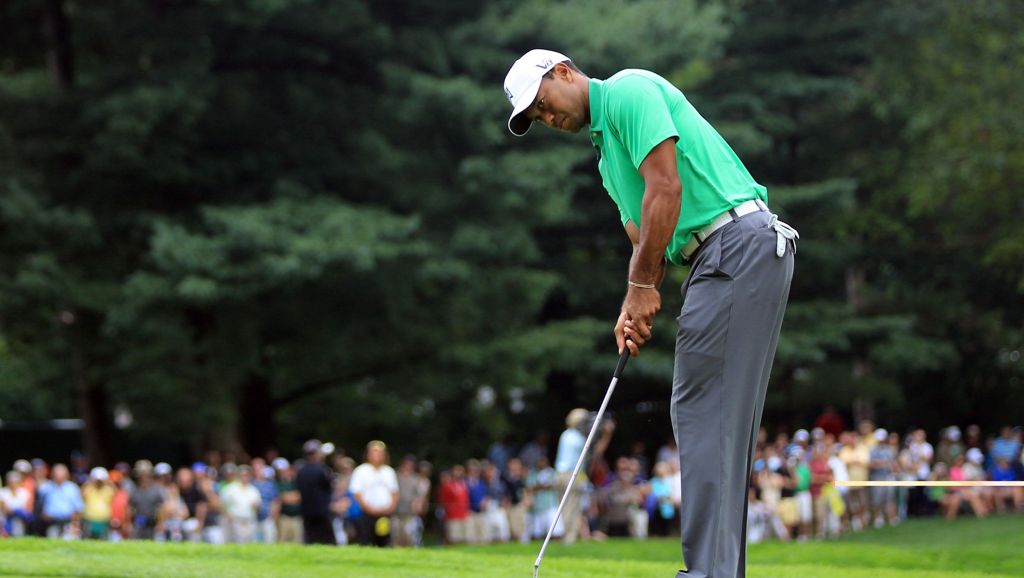 Tiger Woods puts on No. 3.