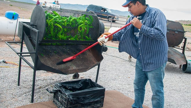 """Marcos Salazar of Hatch-based Salazar Produce roasts chiles at the 2015 Hatch Chile Festival on Saturday."""""""