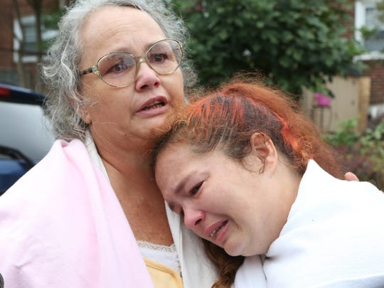 Missy Napier, a resident who escaped a house fire where two Wilmington firefighters died, is consoled at the fire scene by her mother, Debby Napier, on Saturday. Fire officials said four firefighters fell when a floor collapsed.