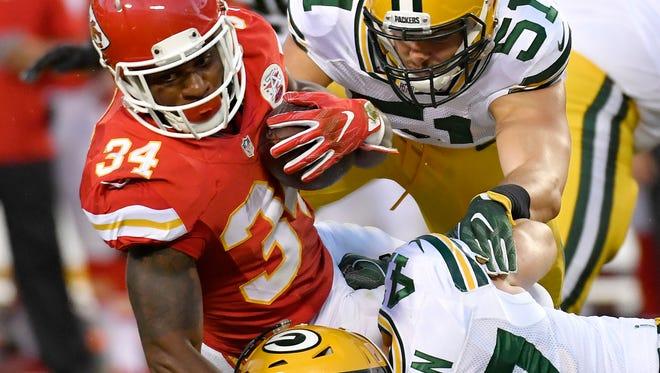 Kansas City Chiefs running back Knile Davis is brought down by Green Bay Packers outside linebacker Kyler Fackrell and inside linebacker Jake Ryan.