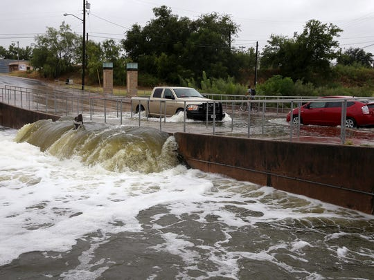 Water pours over the Irving Street bridge into the