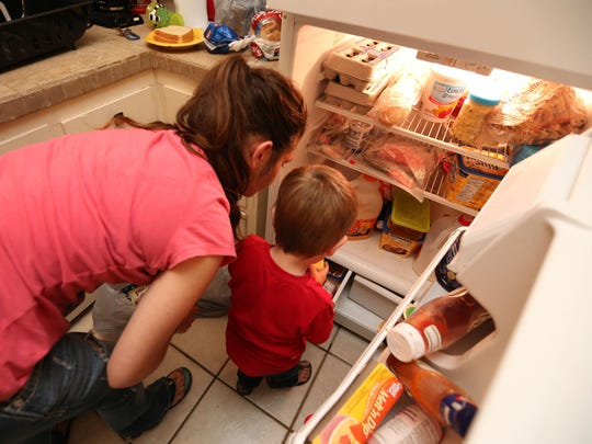 Anna Sommer and her son, Isaiah, 2, put groceries away on Wednesday. She recently moved into an apartment from the Missouri Hotel and relies on WIC and Temporary Assistance for Needy Families to provide for her two young boys. The Republican-controlled state Legislature passed a law lowering the amount of time families could stay on the TANF program from 60 to 45 months.