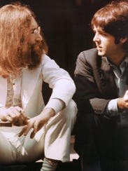 John Lennon, left, and Paul McCartney talk during the