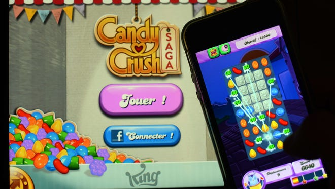 A man plays 'Candy Crush Saga' on his iPhone.