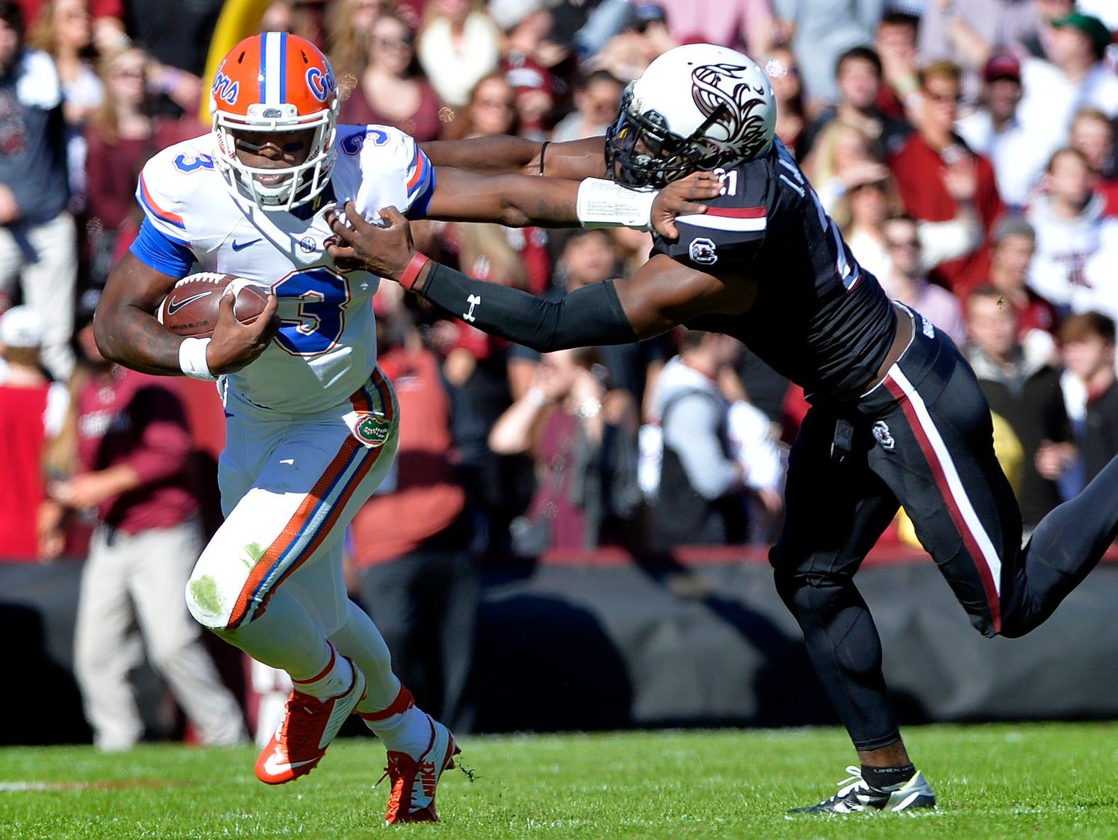 Florida quarterback Treon Harris (3) stiff-arms USC linebacker T.J. Holloman (11) and gets the first down at Williams-Brice Stadium in Columbia on Nov. 14, 2015.