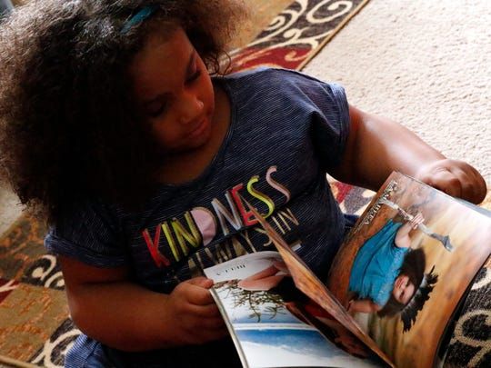 La'Mareea Waddell flips through a modeling book that features a picture of her taken by photographer Leslie Dye.