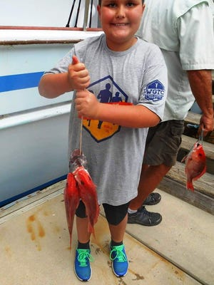 Julian Chiesa, who was visiting from Sharpsburg, Georgia, shows off his red snapper catch.