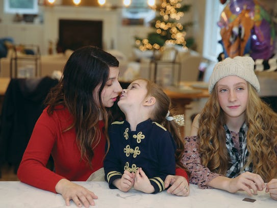 Maria Hays snuggles with her daughter Lucy, 5, in the kitchen of their new home on Thursday. The Hays family moved into their new home on Christmas Eve after their old home burned in a 2016 fire. On the right is daughter Ava, 14.