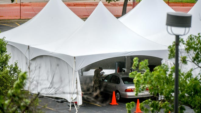 A member of the Illinois National Guard helps get a client set up for COVID-19 testing on June 10 at the Peoria Civic Center site in Downtown Peoria.